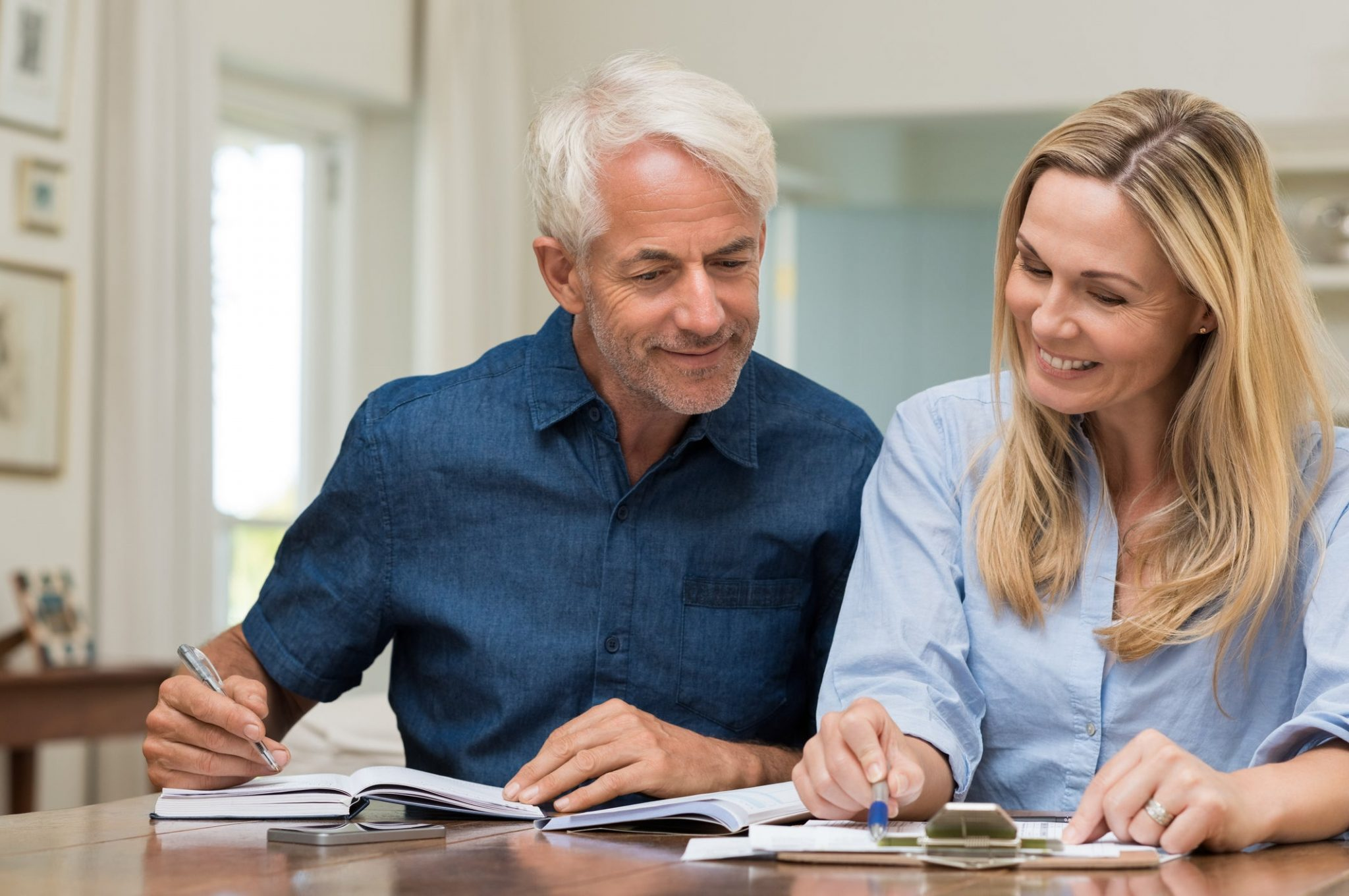 mature-couple-discussing-finances-with-pens-and-paper